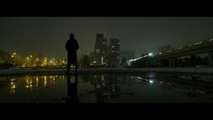 Foto mit schwarzer Siluette im Hintergund eine Stadt bei Nacht