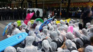 Demonstration mit Schlauchbooten und weißen Plastik-Schutzanzügem gegen die Identitären
